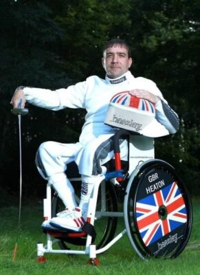 David Heaton, British wheelchair fencer, poses with his mask and sword